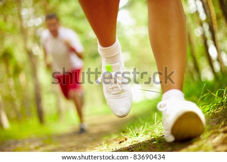 Image of human feet in sportshoes running down grass - stock photo
