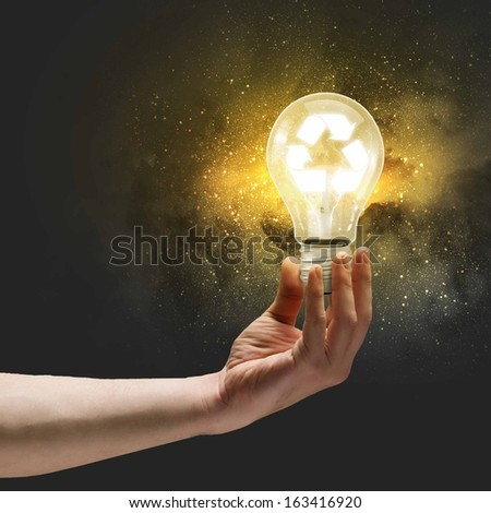 Image of human hand holding bulb with recycle symbol inside - stock photo
