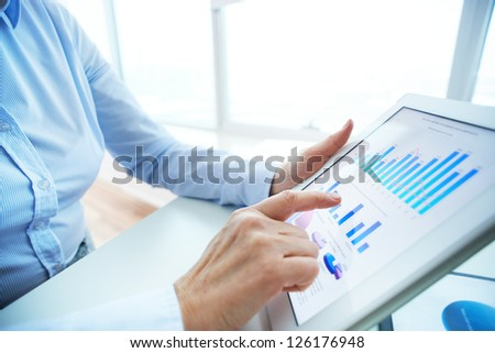 Image of human hand pointing at touchscreen with business document - stock photo