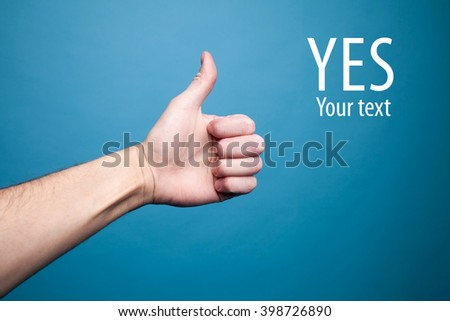 Image of human hand showing thumb up on a blue background