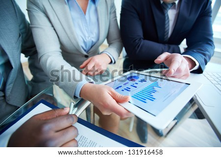 Image of human hands during discussion of business document in touchscreen - stock photo