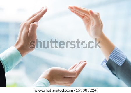 Image of human hands making a circle taking care from something on the foreground - stock photo