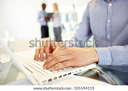 Image of human hands typing in the foreground, business colleagues can be recognized in the blurred background