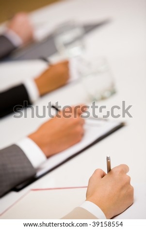 Image of human hands with pens over business documents