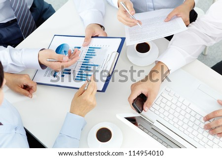 Image of human hands with pens over business documents at meeting