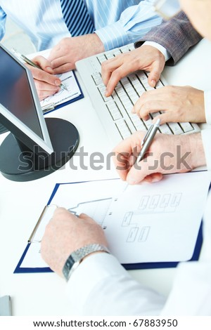 Image of human hands working with papers and typing on keyboard