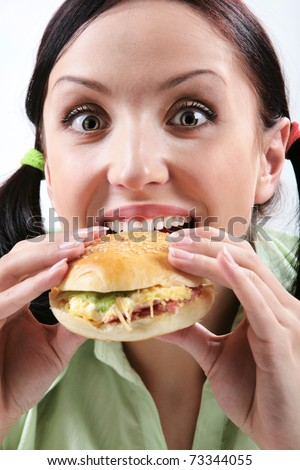 Image of hungry girl eating hamburger and looking at camera
