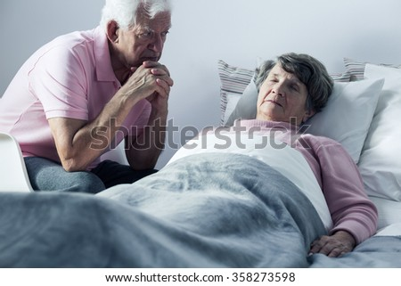 Image of husband and mortally ill wife at hospice - stock photo