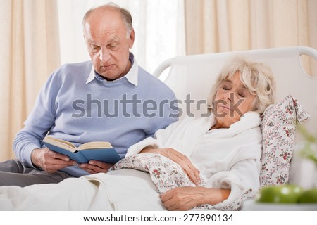 Image of husband reading ill wife book - stock photo