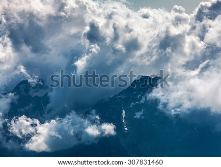 Image of impressive clouds gathering over the high mountain peaks in The Alps. - stock photo