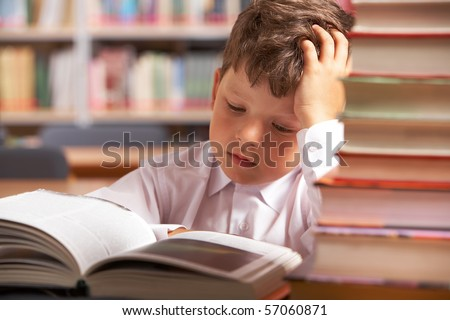 Image of interested schoolkid reading book in the library