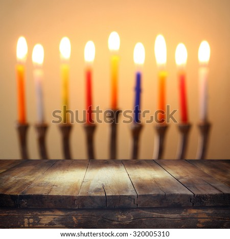 Image of jewish holiday Hanukkah background with menorah (traditional candelabra) Burning candles over wooden table   - stock photo