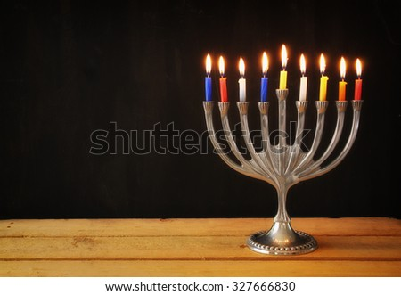 Image of jewish holiday Hanukkah background with menorah (traditional candelabra) Burning candles over black background   - stock photo