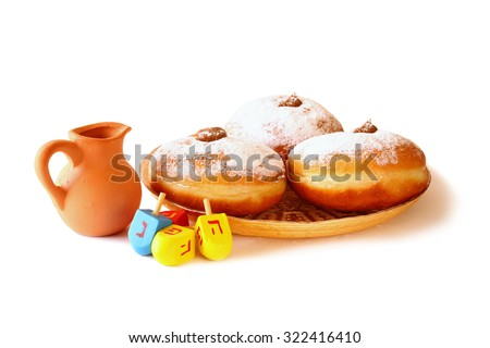 image of jewish holiday Hanukkah with donuts, traditional chocolate coins and wooden dreidels (spinning top). isolated on white  - stock photo