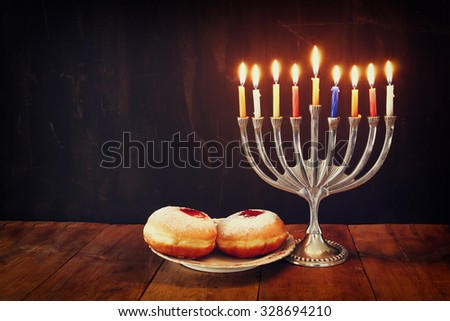 image of jewish holiday Hanukkah with menorah (traditional Candelabra) and donuts  - stock photo