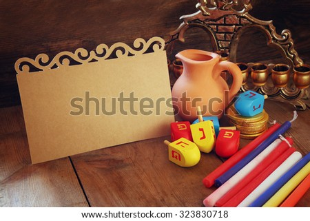 image of jewish holiday Hanukkah with menorah (traditional Candelabra) and wooden dreidels (spinning top) with empty card for adding text. retro filtered image  - stock photo