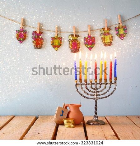 image of jewish holiday Hanukkah with menorah (traditional Candelabra) and wooden dreidels (spinning top). glitter overlay  - stock photo