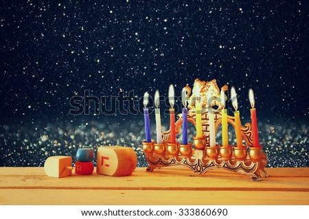 image of jewish holiday Hanukkah with menorah (traditional Candelabra) and wooden dreidels (spinning top) on table - stock photo