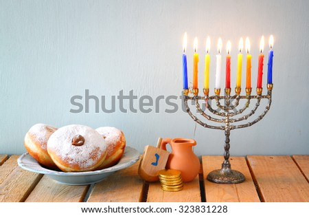image of jewish holiday Hanukkah with menorah (traditional Candelabra), donuts and wooden dreidels (spinning top)  - stock photo
