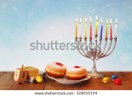image of jewish holiday Hanukkah with menorah (traditional Candelabra), donuts and wooden dreidels (spinning top). glitter overlay  - stock photo