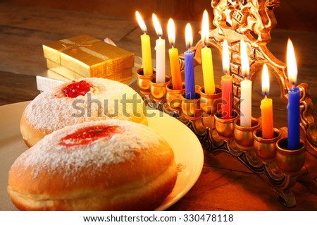 image of jewish holiday Hanukkah with menorah (traditional Candelabra), donuts and wooden dreidels (spinning top). retro filtered image  - stock photo