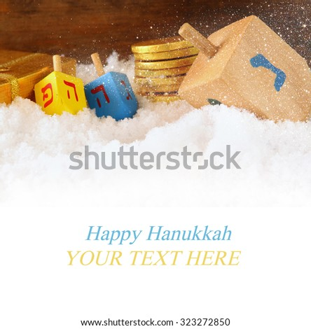 image of jewish holiday Hanukkah with wooden colorful dreidels (spinning top) and chocolate traditional coins over december snow. copy space  - stock photo