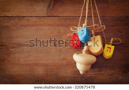 image of jewish holiday Hanukkah with wooden colorful dreidels (spinning top) hanging on a rope over wooden background  - stock photo