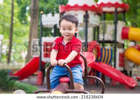 Image of joyful boy having fun on playground outdoors. Happy little three years old child boy rocking and laughing - stock photo