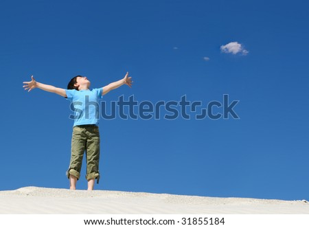 Image of joyful boy in casual clothes standing on sand with his arms outstretched - stock photo