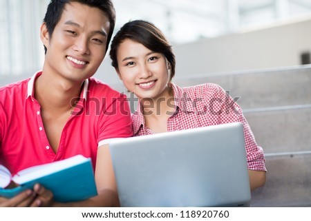 Image of joyful college students getting knowledge from different sources �¢?? a book and a laptop - stock photo
