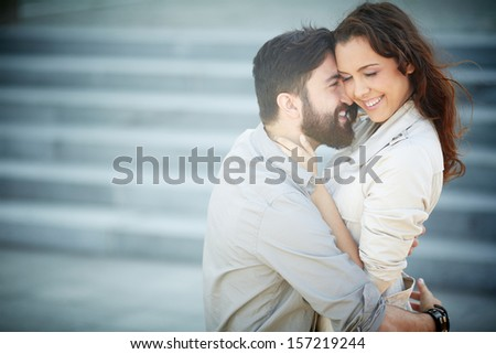 Image of joyful dates embracing outside