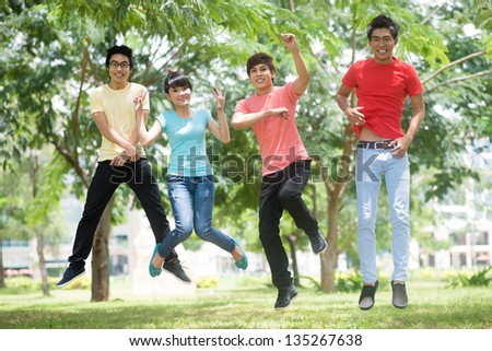Image of jumping friends in the park - stock photo