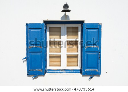 image of lantern, windows and blue shutters on the background of white wall on a sunny day. Greece