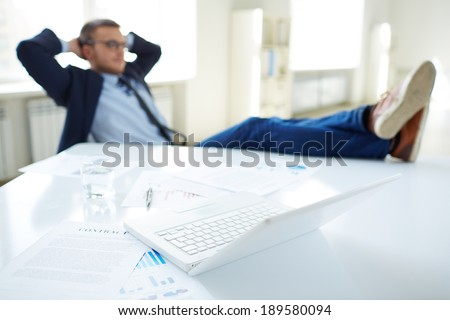 Image of laptop at workplace and businessman relaxing in office - stock photo
