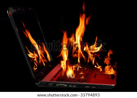 Image of laptop with fire burning from being over-used - stock photo