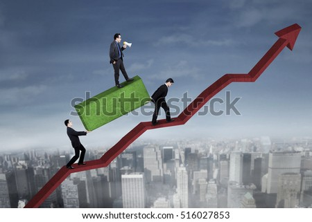Image of leader with megaphone commanding his employees to bringing boulder while walking in the upward red arrow