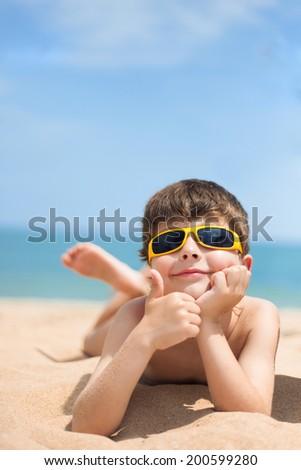 Image of little boy lying on the beach - stock photo