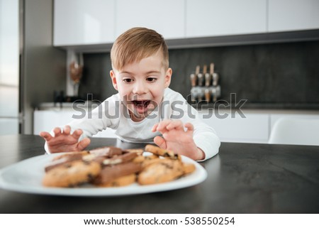 Image of little boy standing in kitchen while tries to eating cookies and chocolate.