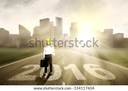 Image of little engineer wearing helmet and holding blueprint with suitcase, standing on the road with numbers 2016 - stock photo