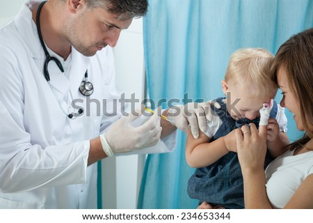 Image of little girl having applied injection - stock photo