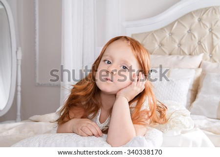 image of little girl with red hair wearing white dress holding hand near her cheek and thinking - stock photo