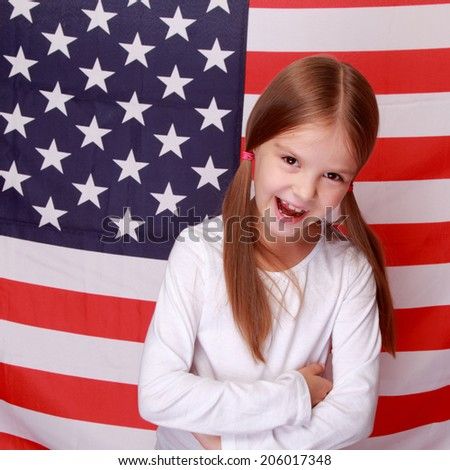 Image of lovely happy smiling little girl on the background of a large U.S. flag/American patriotism