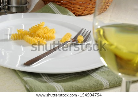 Image of macaroni served in a plate with white wine