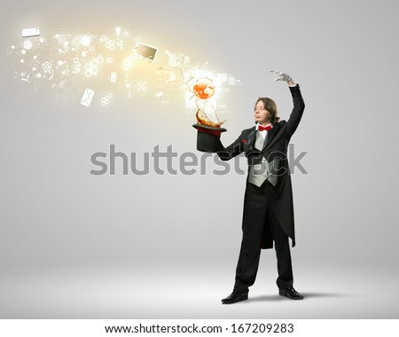 Image of magician with hat and computer devices flying in air
