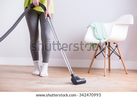 Image of maid vacuuming floor in house