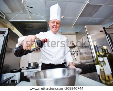 Image of male chef pouring dressing into bowl in the kitchen