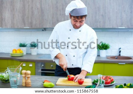Image of male chef with knife cutting vegs on wooden board - stock photo