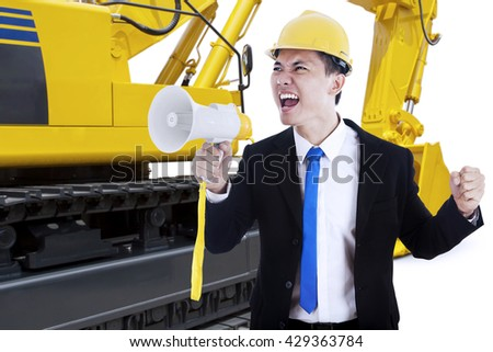 Image of male contractor screaming with a megaphone and an excavator on the background