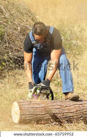 Image of male cutting wood with chainsaw.  Image taken on a family trip to cut firewood in Northern California.