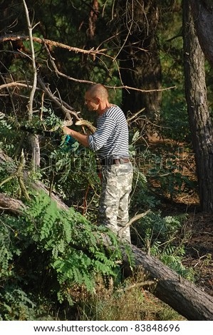Image of male cutting wood with chainsaw.Ukraine - stock photo